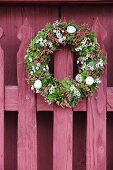 Festive Easter wreath on traditional red picket fence