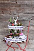 Easter flower arrangement on cake stand on red garden chair