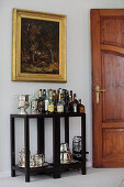 Drinks table below gilt-framed painting on wall