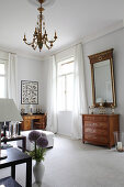 Antique chest of drawers below gilt-framed mirror on wall in lounge