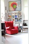 Red armchair and bookcase in study