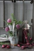 Vintage-style arrangement of zinc pots, snake's head fritillaries, onions and swing-top bottle
