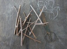 Twigs, vintage scissors and wire on rustic wooden surface