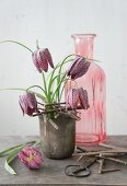 Flower stand hand-made from twigs on pot and snake's head fritillaries