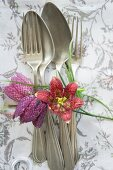 Vintage silver cutlery and flowers on linen napkin