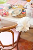 White paper flower on chair backrest