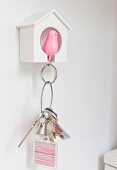 Pink bird key chain pendant hung up in small white birdhouse