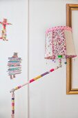 Standard lamp with crocheted cover on stand and floral lampshade