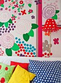 Various scatter cushions in front of colourful wall decorated with large floral motifs
