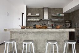 Cast concrete kitchen counter and silver bar stools in open-plan kitchen