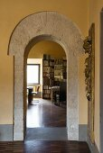 View of parquet floor and bookcase in living area seen through stone archway