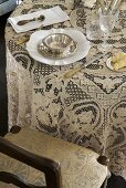 Lace tablecloth and vintage place setting next to upholstered chair