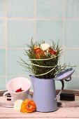 Arrangement of ranunculus and bilberry twigs in old enamel coffee pot