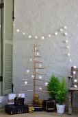 Presents below stylised Christmas tree made from copper piping and decorated with paper stars