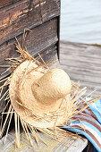 DIY-Strohhut an Holzwand gelehnt