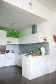 Open-plan kitchen with white cabinets and grey splashback