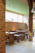 Moderne Holztische vor rustikalen Backsteinwänden und Holzbalken