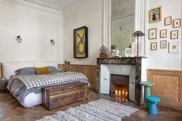 Schlafzimmer in einem Altbau mit Kassettenverkleidung und Kamin