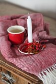 White candle in red candlestick with rose hips next to mug on fringed blanket