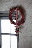 Wreath of twigs with rose-hip posy hung from red and white ribbon next to window