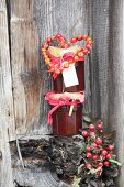 Stacked jars of jam decorated with rose-hip love-heart against rustic board wall