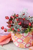 Autumn flower arrangement with rose hips and autumn leaves in pot wrapped in gift wrap