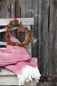 Romantic heart-shaped wreath of rose hips and moss on rustic wooden bench