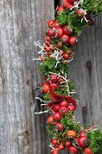 Wreath of rose hips and moss on weathered board wall (detail)
