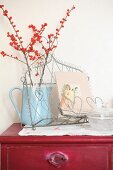 Branches of red berries in pale blue jug and vintage angel motif on wire rack on top of vintage chest of drawers