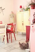 Dining area with red wooden chair, antique pastel yellow cabinet and vintage tailors' dummy