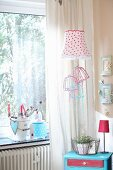 Corner room romantically decorated with red and white lampshades and pastel picture frames
