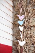 Garland of birds on rustic wall with leafless winter climbing plant