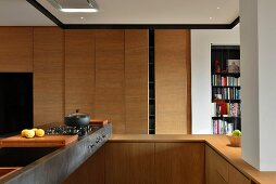 Open-plan, wooden designer kitchen with metal counter and gas cooker