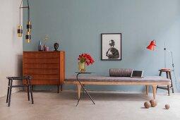 Retro Schubladenkommode neben Tagesliege vor hellblauer Wand