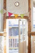 Crocheted bunting hung on half-timbered wall with lattice door