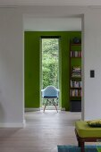 Chair in front of narrow window in green wall
