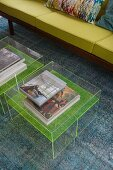 Art books on transparent coffee tables in front of green sofa