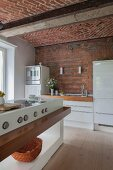 Brick wall and vaulted ceiling in kitchen with white glossy cabinets