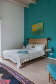 Simple bed in bedroom with high ceiling and blue wall