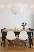 Spherical feathered lampshade above old wooden table with various chairs