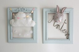 Two blue frames decorated with lettering, cloud mobile and rabbit mask