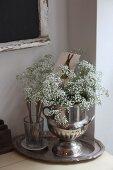 Bouquet of gypsophila in silver urn
