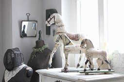 Toy horses on old cabinet next to tailors' dummies