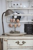 Eggs on metal stand on chest of drawers below plate rack on wall