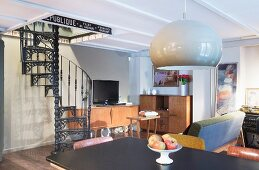 View across dining table in retro-style interior with cast iron black spiral staircase
