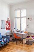 Red designer chair and modern desk below window