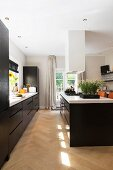 Large kitchen with black cabinets and white worksurface