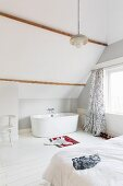 Free-standing bathtub under sloping bathroom ceiling