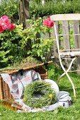 Picnic basket, blanket, enamel crockery and wreath of wildflowers in garden