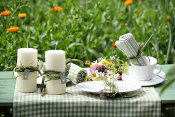 Candles and posy of wildflowers arranged on garden table